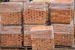 Staplungsziegelsteine des roten Lehms auf Paletten Stockbilder