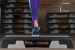 Stapplatform voet op stapplatform Klassen in de gymnastiek geschiktheidsaerobics stock foto's