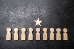 A star above a person who stands in a row among other people. Wooden figurines. The concept of a sign of distinction, success. Achievement and career growth Stock Image