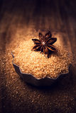 Star Anise and  brown cane sugar on wooden background, Royalty Free Stock Photo