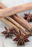 Star anise and cinnamon on a chopping board. A composition with some star anise in the foreground and three cinnamon sticks on a wooden chopping board, slightly Stock Photography