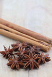 Star anise and cinnamon on a chopping board. A composition with some star anise and two cinnamon sticks on a wooden chopping board, space for text on top Royalty Free Stock Photography