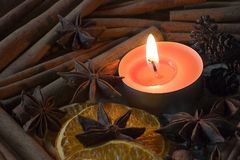 Star anise, cinnamon and orange, when lit candle Royalty Free Stock Photo