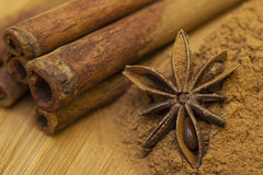 Star anise with cinnamon stick an cinnamon powder on  wooden table. Stock Images