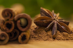 Star anise with cinnamon stick an cinnamon powder on  wooden table. Royalty Free Stock Images