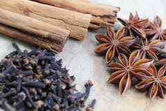 Star anise, cinnamon sticks and cloves on a chopping board Royalty Free Stock Photo