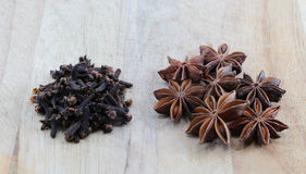 Star anise and cloves on a chopping board. A composition with some star anise and some cloves on a wooden chopping board, space for text, landscape cut Stock Photos