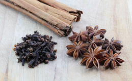 Star anise, cloves and cinnamon on a chopping board. A composition with some star anise, some cloves and two cinnamon sticks on a wooden chopping board Royalty Free Stock Image