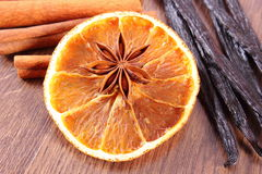 Star anise, fragrant vanilla, cinnamon and dried orange on wooden surface Stock Photography