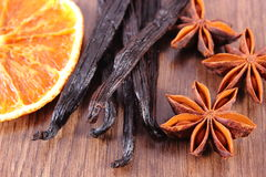 Star anise, fragrant vanilla and dried orange on wooden surface Stock Photo
