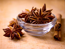 Star Anise in the Glass Bowl and Cinnamon Sticks on Wooden Table Royalty Free Stock Images