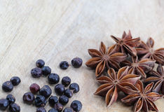 Star anise and juniper berries on a chopping board. A composition with some star anise and some juniper berries on a wooden chopping board, landscape cut Stock Photos