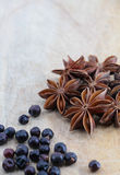 Star anise and juniper berries on a chopping board. A composition with some star anise and some juniper berries on a wooden chopping board, space for text Stock Photo