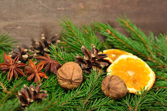 Star anise, nuts, cones, dried oranges and spruse branch on a wo Stock Photos