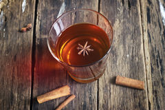 Star anise in tea glass vibrant on wooden and cinnamon background. Star anise in tea glass vibrant on wooden and cinnamon Royalty Free Stock Image