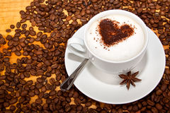 Star aniseed and cacao heart in coffee Stock Photos
