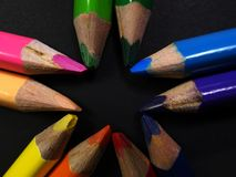 Star array. Colored pencils array in a dark paper background stock images