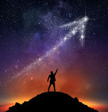 Star arrow upwards. Businessman on a mountain indicate an arrow with stars royalty free stock image