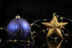 Star, bauble and lights. Christmas decoration, blue and silver bauble, gold glitter star and fairy lights against a black background royalty free stock images