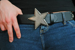 Star Belt Buckle. A star shaped belt buckle on a leather belt worn by a girl in denim jeans Stock Photography