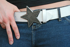 Star Belt Buckle. A star shaped belt buckle on a white leather belt worn by a girl in denim jeans royalty free stock photography