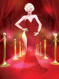 A star is born. This classic blonde bombshell walks  the red carpet and dazzles Hollywood with her red, couture fashion dress and stunning figure Royalty Free Stock Photo