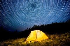 Star círculos acima da floresta da montanha da noite e de uma barraca de acampamento de incandescência foto de stock