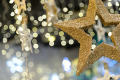 Star Christmas ornament on blurred background. Metallic gold star Christmas ornament on shimmering blurred background Stock Image