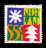 Star and christmas tree, December stamps serie, circa 1994. MOSCOW, RUSSIA - MAY 13, 2018: A stamp printed in Netherlands shows Star and christmas tree, December Royalty Free Stock Photo