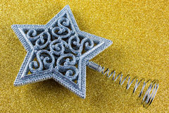Star Christmas tree top. Star shaped Christmas tree top decoration in silver on sparkling gold background Stock Photos