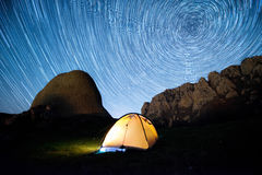 Star circles above the mountains and a glowing camping tent. Crimea, Demerdzhi. 69 shots: Long exposure - 43 seconds, ISO 640, f/2.8, 14mm. March 2017 Stock Photo