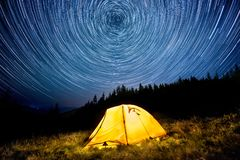 Star circles above the night mountain forest and a glowing camping tent.  stock photo