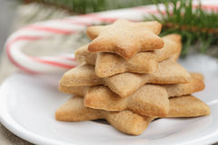 Star cookies and candy cane on table Stock Photos