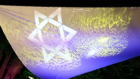 Star of David. Dynamic light projection on canvas outdoor in the night stock video