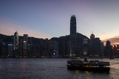 Star Ferry and lit skyscrapers in Hong Kong at dusk Stock Photo