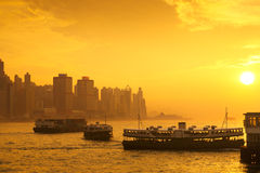 Star ferry. Passenger boats at sunset in victoria harbour, Hong kong Stock Photos