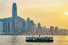 Star ferry at Victoria Harbor and Hong Kong skyline at sundown Stock Photography