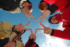 Star of fingers team. Snowboard team making a finger star in the blue ski as background Royalty Free Stock Photography