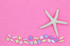 Star fish, known as sea stars, and marine life beads on pink fin Stock Photography
