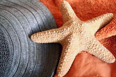 Star-fish on towel. Still-life of things featured to holiday on the beach: straw-hat, towel,star-fish stock image