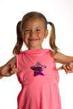 Star girl. Little girl pointing to the star on her dress and grinning Stock Images