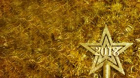 Star golden color decoration on the Christmas tree. On a background of golden background with numbers 2018 Royalty Free Stock Photos