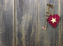 Star heart and antique bronze skeleton key hanging on rustic wood door Stock Images