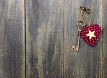 Star heart and antique bronze skeleton key hanging on rustic wood door. Red heart and bronze skeleton key hanging on rustic wooden sign Stock Images