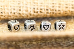 Star and heart symbol cube beads on sockcloth Stock Image