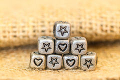 Star and heart symbol cube beads on sockcloth Royalty Free Stock Photos