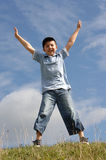 Boy with outstretched arms. A boy star jumping on hill stock photo