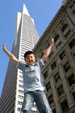 A star jumping boy in a city landscape. A boy with outstretched arms with a city back drop royalty free stock images