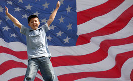 A Star jumping boy in front of usa flag. A cheering boy in front of american flag stock image