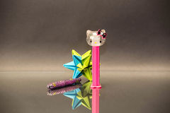 Star and kitty. A paper star, a pen and a hello kitty pez disposer Royalty Free Stock Images